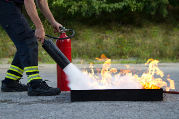 Instructor showing how to use a fire extinguisher on a training fire